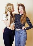 Blond tonårs- flicka som två bedrar omkring att röra till hår Royaltyfri Foto