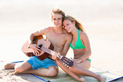 Blond tourist couple playing guitar at beach Stock Images
