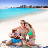 Blond tourist couple playing guitar at beach. Blond young tourist couple playing guitar at beach in Mexico Caribbean photo mount Royalty Free Stock Photos