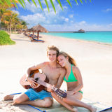 Blond tourist couple playing guitar at beach Stock Photo