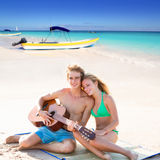Blond tourist couple playing guitar at beach Stock Photography