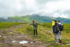 The blond tourist girl with a backpack standing on mountain rest stock images