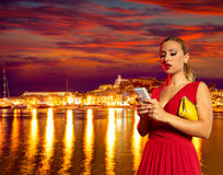 Blond tourist girl smartphone chat in Ibiza sunset Royalty Free Stock Image
