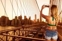 Blond tourist girl taking photo in Brooklyn Bridge Stock Photos