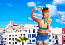 Blond tourist girl taking photos of Ibiza skyline Stock Photo