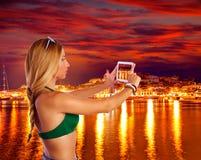 Blond tourist girl taking photos of Ibiza skyline Royalty Free Stock Photos