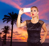 Blond tourist girl taking photos of Mallorca sunset. Blond tourist girl taking selfie photo Mallorca Arenal beach sunset photomount Stock Photos