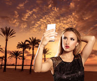Blond tourist girl taking photos of Mallorca sunset. Blond tourist girl taking selfie photo Mallorca Arenal beach sunset photomount Stock Photo