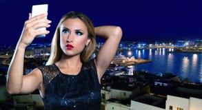 Blond tourist girl taking selfie photo in Ibiza skyline Stock Photography