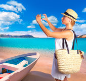 Blond tourist in Mallorca beach taking photos Stock Images