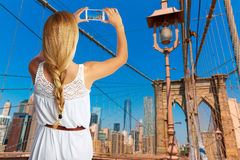 Blond tourist taking photo in Brooklyn bridge NYC stock photo
