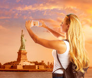 Blond tourist taking photo to Statue of Liberty NYC Stock Photography