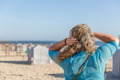 A blond tourist woman observes placidly the landscape, while on a beautiful white sand beach, on a summer day. A blond tourist woman observes the landscape royalty free stock photos