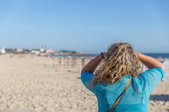 A blond tourist woman observes placidly the landscape, while on a beautiful white sand beach, on a summer day. A blond tourist woman observes the landscape stock images