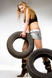 Blond with tyres Royalty Free Stock Photography