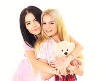 Blond und Brunette auf lächelnden Gesichtern in der Kleidung für Schlaf schaut nett und freundlich Mädchen Umarmen, lokalisiert a Lizenzfreie Stockbilder