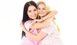 Blond und Brunette auf lächelnden Gesichtern in der Kleidung für Schlaf schaut nett und freundlich Schwestern oder beste Freunde  Stockbilder
