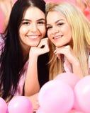 Blond und Brunette auf lächelnden Gesichtern haben Sie Spaß an der inländischen Partei Mädchen legen auf Bauch nahe Ballonen, ros Stockbilder