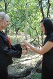 Blond und Brunette im Holz mit Samuraisäbel Lizenzfreie Stockfotos