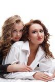 Blond und Brunette liegend in der Bettatelieraufnahme Lizenzfreie Stockfotografie