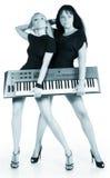 Blond und Brunette mit elektrischem Klavier Stockfotos