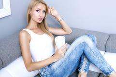 Blond ung kvinna som hemma kopplar av Royaltyfri Bild