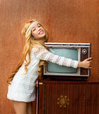 Blond vintage 70s kid girl with retro love old tv Stock Images
