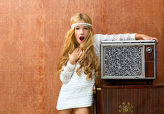 Blond vintage 70s kid girl with retro love old tv. Blond vintage 70s kid girl with retro wood tv surprised expression gesture Stock Images