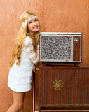 Blond vintage 70s kid girl with retro love old tv Royalty Free Stock Photo