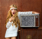 Blond vintage 70s kid girl with retro tv. Blond vintage 70s kid girl with retro wood tv surprised expression gesture Royalty Free Stock Images