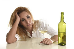 Blond wasted and depressed alcoholic drunk woman drinking white wine glass desperate sad Stock Photos