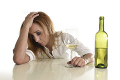 Blond wasted and depressed alcoholic drunk woman drinking white wine glass desperate sad. Caucasian blond wasted and depressed alcoholic woman drinking white Stock Image