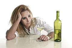 Blond wasted and depressed alcoholic drunk woman drinking white wine glass desperate sad. Caucasian blond wasted and depressed alcoholic woman drinking white Royalty Free Stock Image