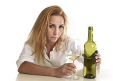 Blond wasted and depressed alcoholic drunk woman drinking white wine glass desperate sad. Caucasian blond wasted and depressed alcoholic woman drinking white Royalty Free Stock Photos