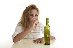 Blond wasted and depressed alcoholic drunk woman drinking white wine glass desperate sad. Caucasian blond wasted and depressed alcoholic woman drinking white Stock Photography