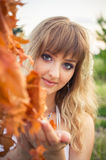 Blond in white dress holding red leaves Royalty Free Stock Photo