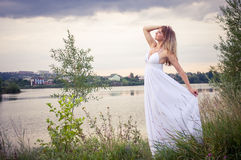 Blond in white dress near the river Stock Photography
