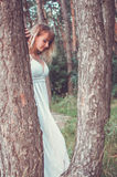Blond in white dress stand between the pines Royalty Free Stock Images
