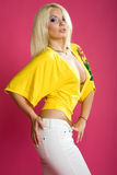 Blond in white fitting skirt and yellow shirt Royalty Free Stock Image