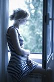 Blond in Window. A blond girl looks out the window Stock Photo