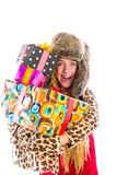 Blond winter kid girl with stacked presents smiling Royalty Free Stock Images