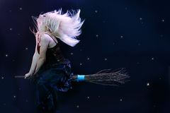 Blond witch flying on broom Royalty Free Stock Image