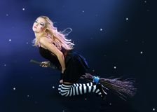Blond witch flying on broom Stock Images