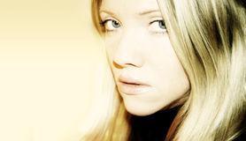Blond Woman. A close-up photo a an unsmiling blond Caucasian woman with long and straight blond hair. She is looking into the camera with her blue eyes and her Stock Photography