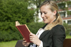 Blond woman. Beautiful young blond busiess woman reading a book stock image