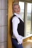 Blond woman. Pretty blond woman wearing casual jeans standing in the doorway Stock Photos
