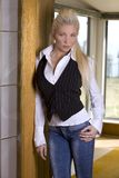 Blond woman. Pretty blond woman wearing casual jeans standing in the doorway Stock Images