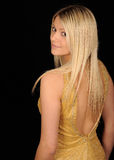 Blond Woman. Attractive blond woman wearing a gold dress with her back to the viewer, looking over her left shoulder toward the viewer.  Isolated against a black Stock Photo