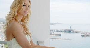 Blond Woman Admiring City View from Balcony stock video