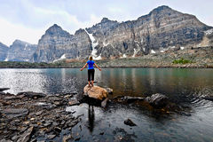 Blond woman by alpine lake enjoying the mountain view on a rainy day. royalty free stock image